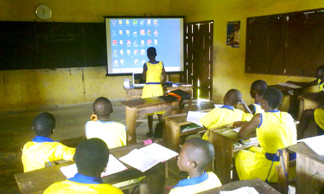 Students learning to use a computer with a single projector
